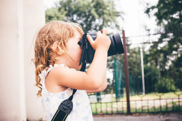 Little girl holding a camera and taking pictures.