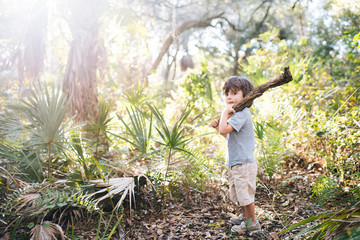 Boy standing in woodland holding tree branch over shoulder