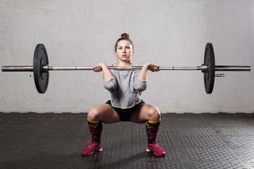 Woman athlete doing a front squat with a barbell  in the gym