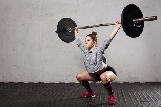 Woman athlete doing a overhead squat  with a barbell  in the  crossfit gym