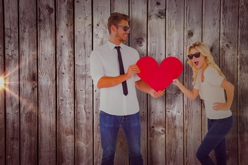 Composite image of cool young couple holding red heart