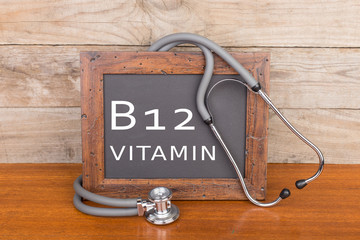 """stethoscope and blackboard with text """"Vitamin B12"""" on wooden background"""