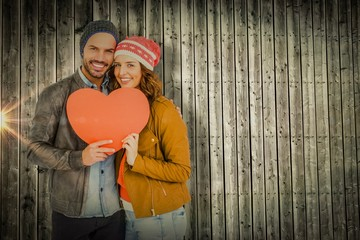 Composite image of young couple holding heart shape paper