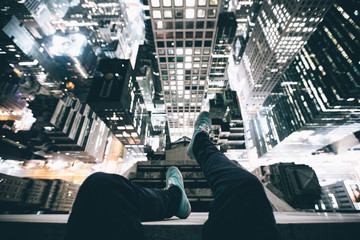 Point of view image of persons legs on top of skyscraper illuminated at night