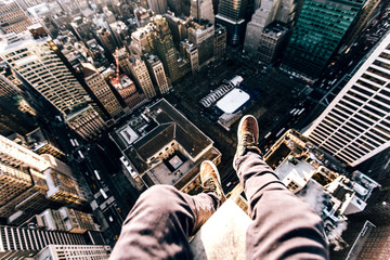 Point of view image of persons legs on top of skyscraper