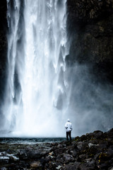 Rear view of person standing by waterfall