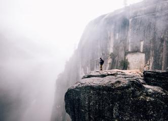 Man standing on cliff in mist