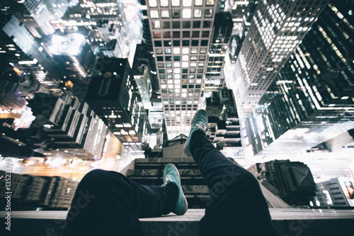 Point Of View Image Persons Legs On Top Skyscraper Illuminated At Night