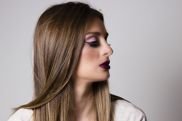 Beautiful woman side portrait. Woman with makeup on her face looking in the distance. Young brunette side portrait. Beautiful hair.