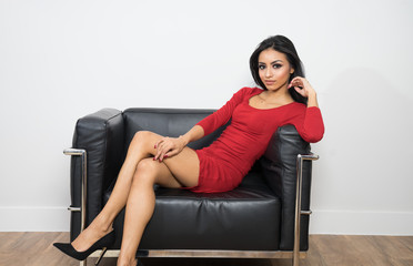 Beautiful woman wearing red dress sitting on black chair