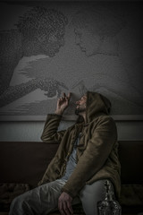 A depressed man in a hood with an empty engraved glass bottle of alcohol sitting, looking back and pointing at his past.