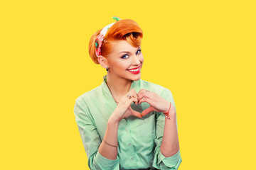 Closeup portrait smiling cheerful happy young woman making heart sign with hands isolated on grey...