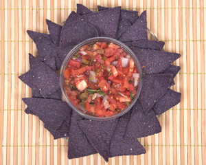 Pico de gallo, authentic mexican salsa in bpa free plastic container and lightly salted organic blue corn tortilla chips isolated on bamboo placemat