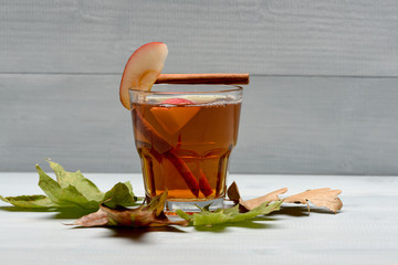 glass with juice, pieces of apple, cinnamon, leaves