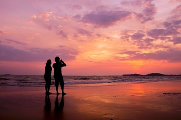 Silhouette of romantic couple standing on the beach at sunset