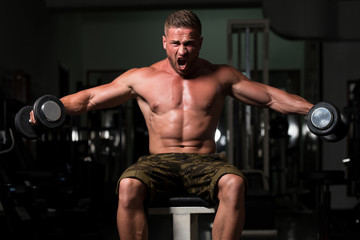 Man In The Gym Exercising Shoulder With Dumbbells