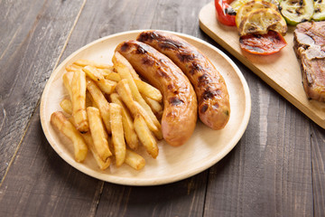 grilled sausage with french fries on wooden background