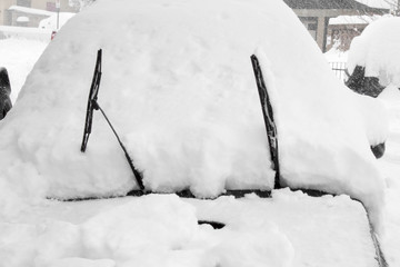 Car buried in snow with it's windshield wipers up to keep them from freezing