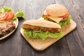 Hot dogs and hamburgers on the wooden background
