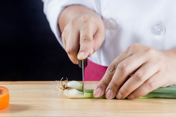 chef chopped green onions or spring onions on wooden board