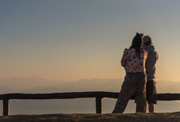 Man and Woman watching the sunrise on the mountain.