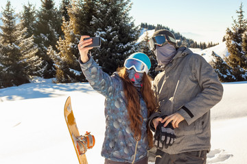 ?ouple snowboarder standing on a mountain top at sunset and maki