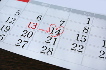 "Calendar page with a red hand written heart highlight and text ""Valentine's Day"" on February 14 of Saint Valentines day."