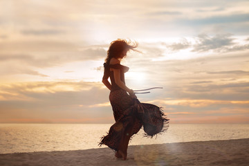 beautiful young woman walking on the beach. woman silhouette at sunset
