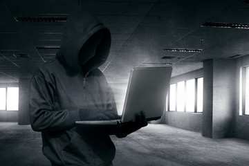 Hooded man with mask using laptop to hacking