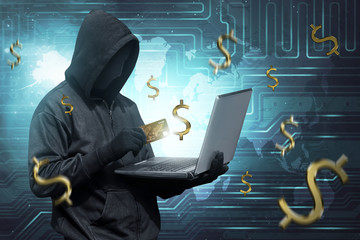 Hacker man with mask holding credit card with laptop on his hand
