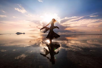 Photo Blinds Dance School Elegant woman dancing on water. Sunset and silhouette.