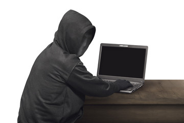 Portrait of hacker man with mask looking back while typing laptop on desk