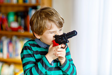 Cute little preschool kid boy playing with gun at home,