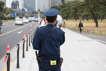 In the picture we can see a Japanese cop announcing and some people are walking in the street and at the background some cars and high rise building can be seen.