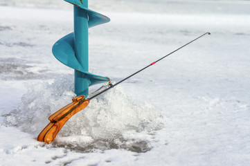 Winter fishing rod and bait on ice background.