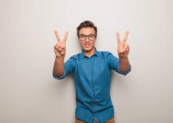 smiling young casual man making victory sign