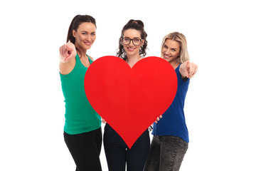 three happy women holding a big red heart pointing fingers