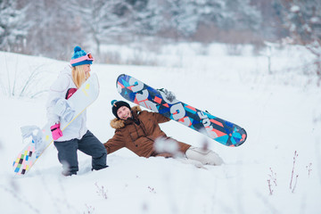 happy couple with snowboards falling in snow