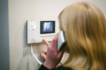 blonde woman hangs up the phone after answering the intercom call in her apartment