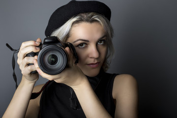 Female professional or amateur photographer holding a dslr camera.  This photographic gear is used by both self employed artists and journalists or for tourism and hobbies.