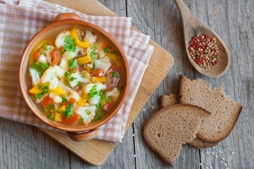 Vegetable soup with bread on wooden table