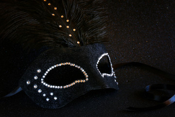 black venetian mask on glitter background