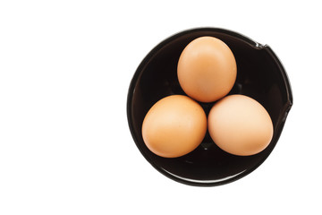 Eggs cooking for breakfast, a protein form yolk and albumen on a white background, or on a plain wooden table.