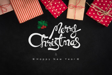 Merry Christmas and Happy New Year text with gift boxes on blackboard background