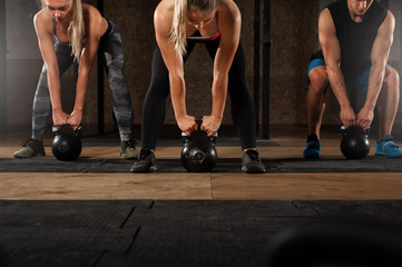 Muscular adults exercising with kettle bell in gym