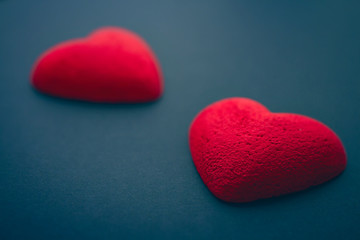 Two bright red hearts on dark blue background, St Valentines Day concept