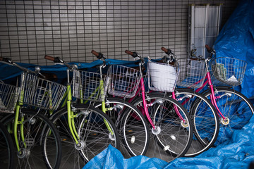 In the image it is seen that bikes are being parked and partially covered with a plastic sheet.