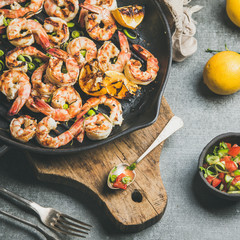 Seafood dinner. Close-up grilled tiger prawns in cast iron grilling pan with lemon, leek, chili pepper and mint salsa sauce over grey concrete background, top view, square crop. Slow food concept