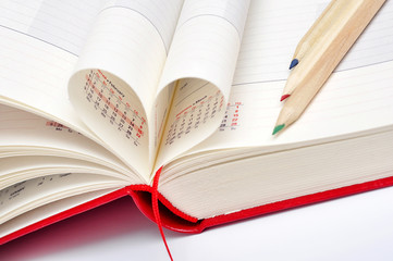 Date in red notebook, heart of pages and color pencils.