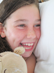 girl child with her blanket lying in bed in fun